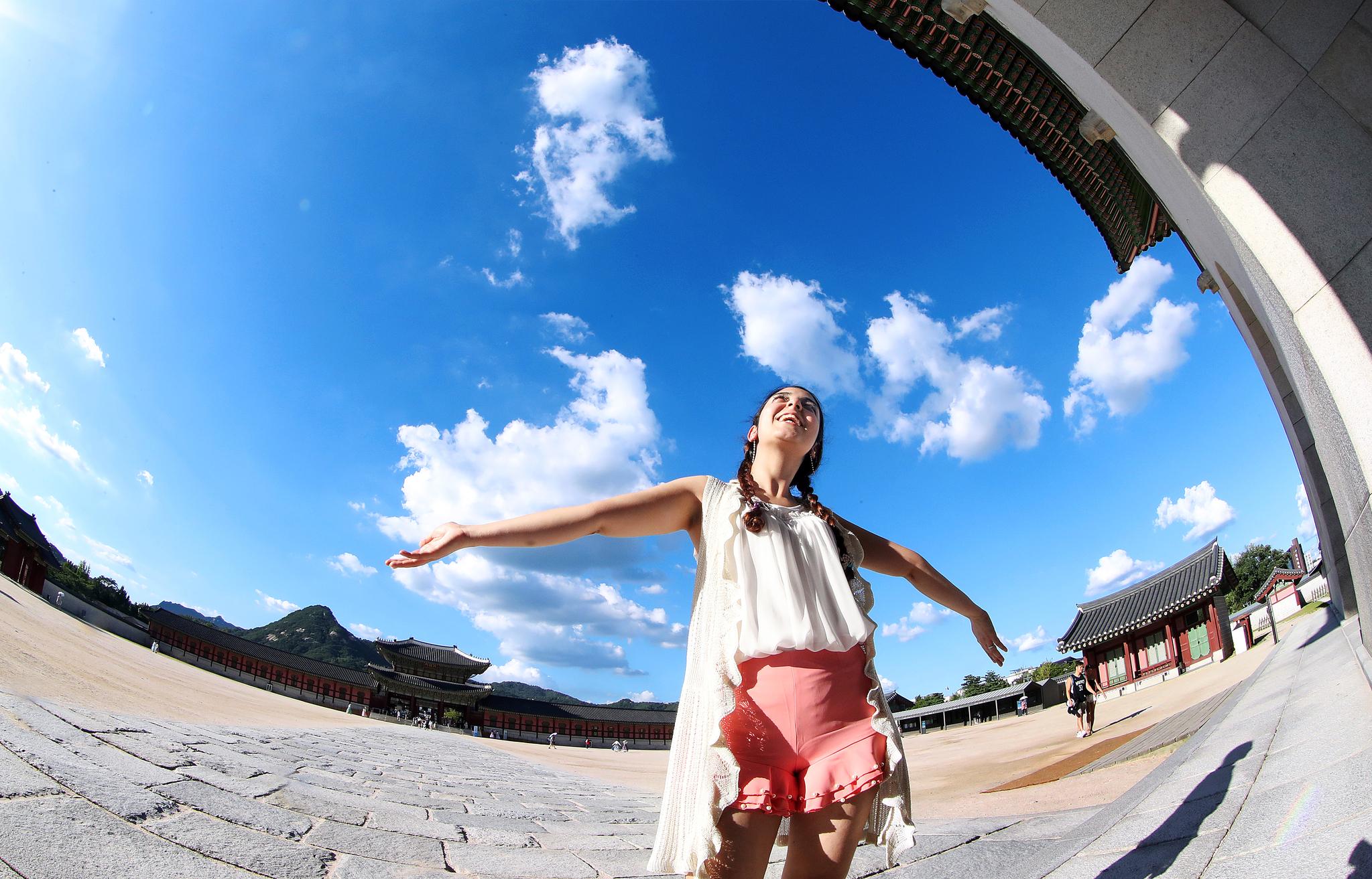 30일 경복궁을 찾은 관광객이 하늘을 배경을 기념사진을 찍고 있다. 우상조 기자