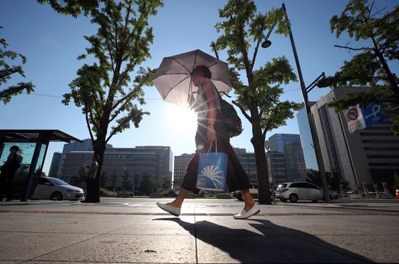 낮 최고기온이 39도까지 오르며 서울지역 역대 최고기온을 경신할 것으로 보이는 1일 오전 서울 광화문 세종로에서 출근길 시민들이 뜨거운 태양을 피해 발걸음을 옮기고 있다. [연합뉴스]