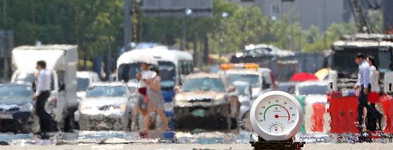1일 강원도 홍천의 최고기온이 41도까지 올라 기상관측이 시작된 이래 111년 만에 가장 높은 기온을 기록했다. 또한 요즘 '서프리카'로 불리는 서울의 최고기온도 1994년의 38.4도를 훌쩍 넘긴 39.6도로 역대 가장 높은 기온을 기록했다. 이날 오후 시민들이 서울 여의도에서 지열로 아지랑이가 피어오르는 횡단보도를 지나가고 있다. 기온과 지열이 더해져 온도계의 바늘이 44도를 가리키고 있다. [뉴스1]