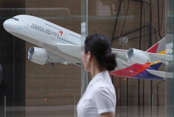 서울 종로구 신문로 금호아시아나 본사 로비에 전시된 모형 항공기 앞으로 한 시민이 걸어가고 있다. [사진 연합뉴스]