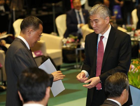 성 김 필리핀주재 미국대사가 4일 오후(현지시간) 싱가포르 엑스포 컨벤션센터에서 열린 아세안지역안보포럼(ARF) 포토세션이 끝난 뒤 리용호 북한 외무상에게 다가가 서류봉투를 전달하고 있다. 오른쪽 아래는 왕이 중국 외교부장. [뉴스1]