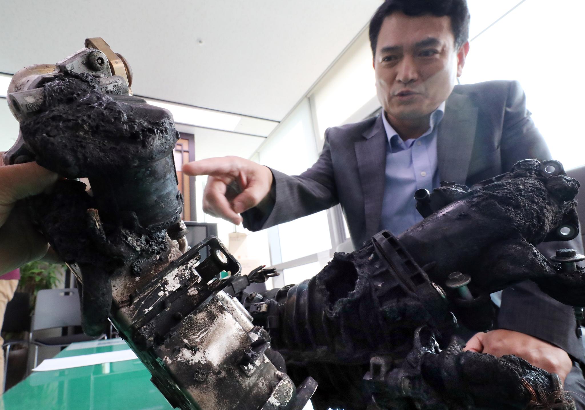 김경욱 국토교통부 교통물류실장이 6일 정부세종청사 국토부 기자실에서 전남 목포에서 안전진단 을 받은 BMW 520d 차량 화재 발생과 관련, 해당차량에서 수거한 배기가스재순환장치(EGR)와 흡기다기관 부품을 공개하고 있다. [뉴스1]
