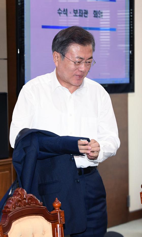 문재인 대통령이 6일 오후 청와대에서 열린 수석보좌관 회의에서 상의 탈의를 하고 있다. 청와대 사진기자단