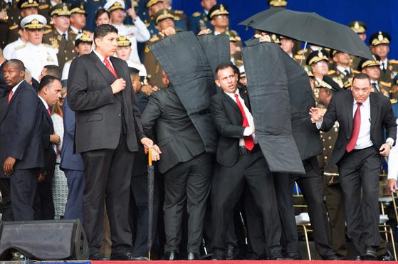 4일(현지시간) 니콜라스 마두로 베네수엘라 대통령의 연설 도중 인근 상공에서 폭발물이 터지자 경호원들이 방탄 장비로 마두로 대통령을 둘러싸고 있다.[신화=연합뉴스]