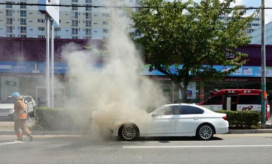 4일 오후 2시 15분께 목포시 옥암동 한 대형마트 인근 도로에서 주행 중인 2014년식 BMW 520d 승용차 엔진룸에 불이 나 연기가 치솟고 있다. [연합뉴스]