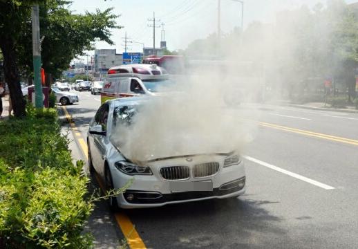 4일 오후 2시 15분께 목포시 옥암동 한 대형마트 인근 도로에서 주행 중인 2014년식 BMW 520d 승용차 엔진룸에 불이 나 연기가 치솟고 있다. [전남 목포소방서 제공=연합뉴스]
