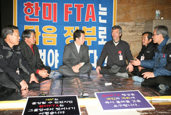 열린우리당 김근태 전 의장이 2007년 3월 27일 한미FTA협상을 다음 정부에 넘길 것을 촉구하며 단식농성에 돌입한 국회 본회의장 앞을 방문한 전농 관계자들과 대화를 나누고 있다. [중앙포토]