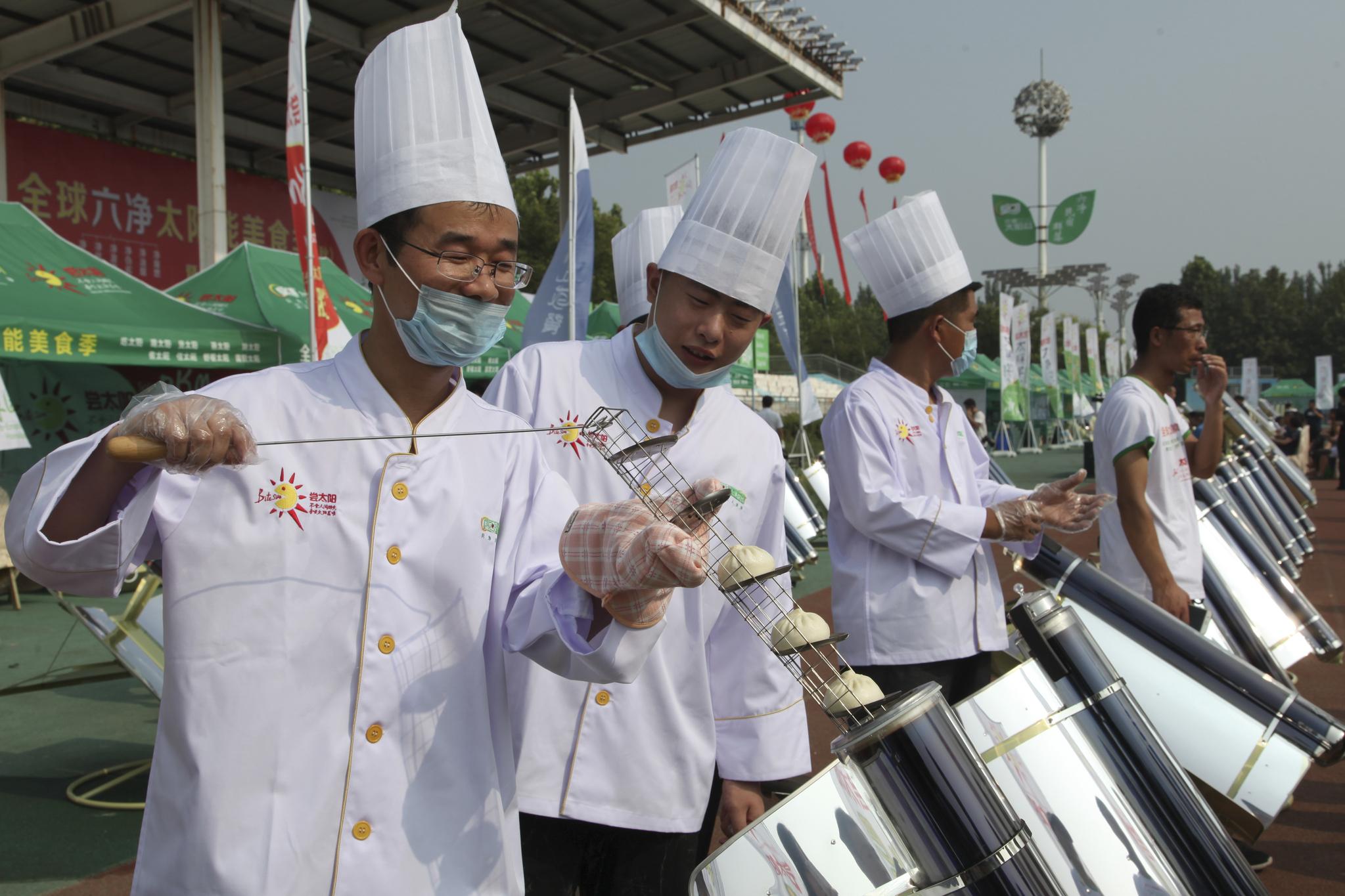 중국 산둥성 더주우시에서 열린 음식축제에서 2일(현지시간) 요리사들이 만두를 굽고 있다. [AP=연합뉴스]