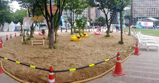 서울광장에서 15톤의 모래사장 위에 야자수와 파라솔이 설치된 미니 인공해변을 마련했다. 정은혜 기자