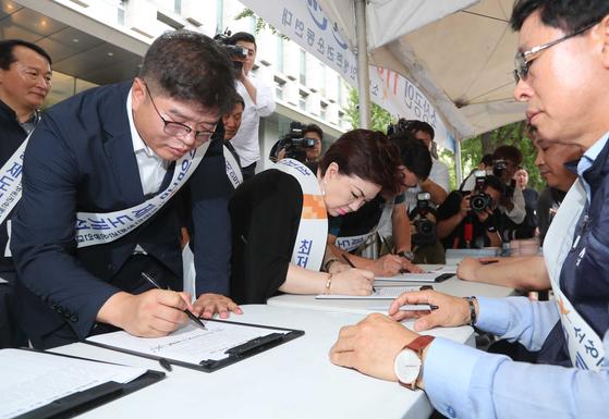 소상공인 119 민원센터 개소식이 9일 서울 광화문 현대해상 앞에서 열렸다. 소상공인들이 최저임금 제도 개선 촉구를 위한 서명을 하고 있다.                               김상선 기자