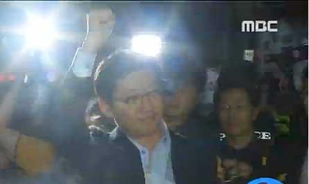 김경수 경남도지사가 10일 새벽 2차 소환조사를 마친 뒤 승용차에 오르기 직전 자신의 지지자들을 향해 주먹을 불끈 취어 보이고 있다. [사진 MBC TV 화면 캡쳐]