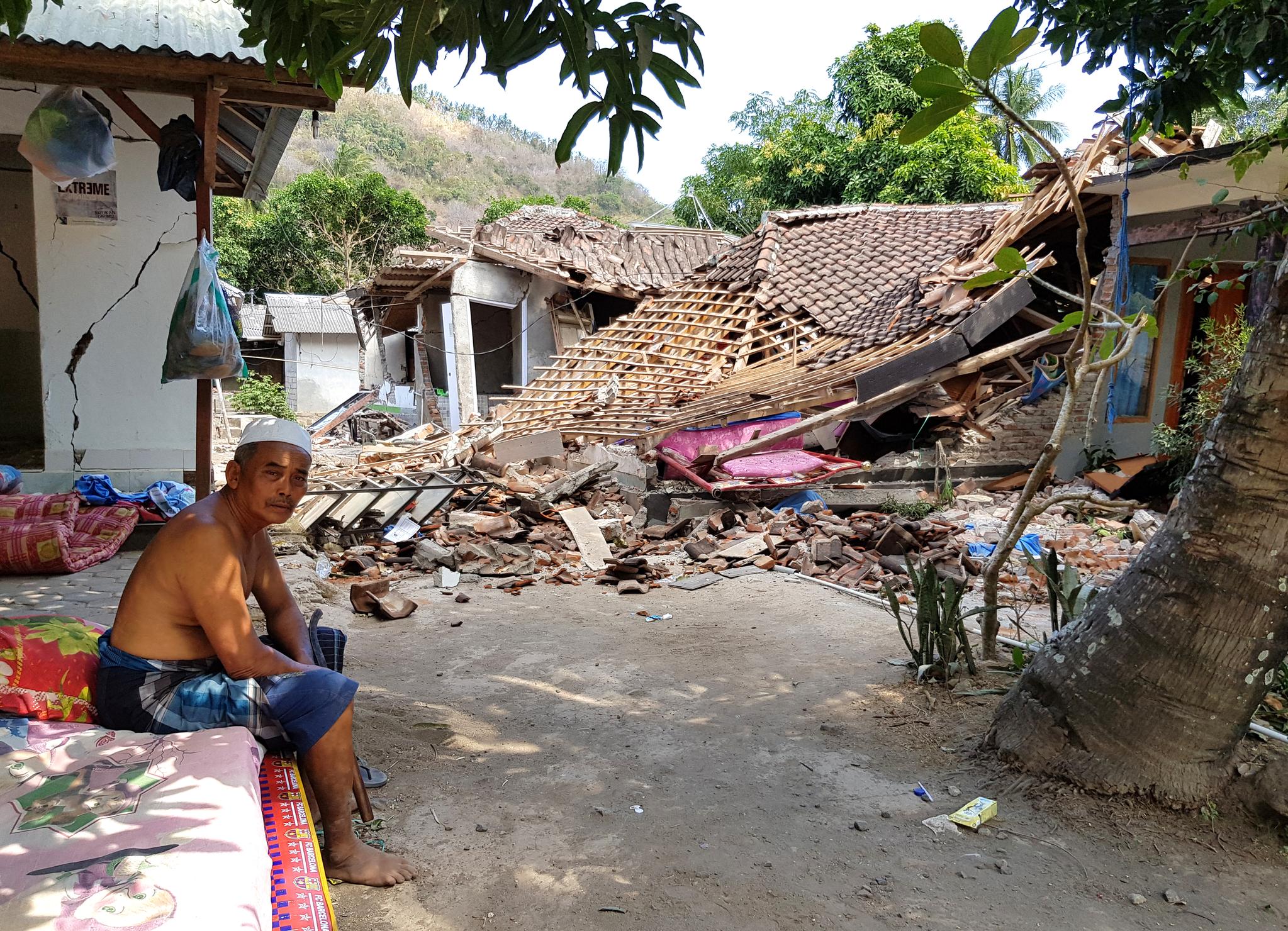 인도네시아의 휴양지인 롬복 섬 북부를 강타한 규모 7.0의 강진으로 사망자 수가 급증하고 있다. 지진 최대 피해지역인 북롬복 방사르항 인근 지대에 한 피난민이 망연자실한 표정으로 앉아 있다. [연합뉴스]