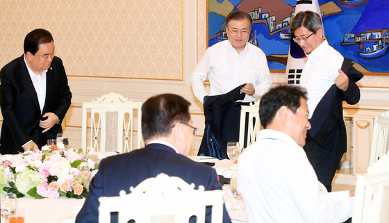 문재인 대통령이 10일 청와대에서 열린 헌법 기관장 초청 오찬에서 윗옷을 벗고 있다. 청와대사진기자단