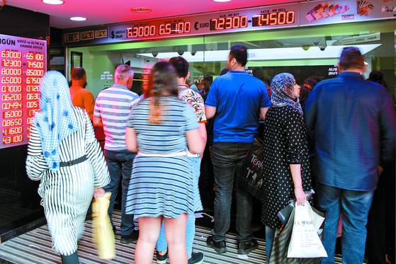 10일 터키 이스탄불에 있는 환전소 앞에 고객들이 줄 서 있다. 이날 달러 대비 터키 리라화 가치가 전날보다 14% 떨어지면서 사상 최저(미 달러당 6.43리라)를 기록하자 환전 수요가 급증했다. [이스탄불 AP=연합뉴스]