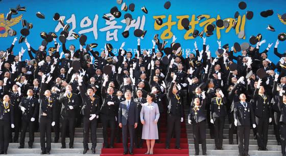 충남 아산시 경찰대학에서 3월 13일에 열린 경찰관 합동임용식. 신입 경찰 간부들이 문재인 대통령 부부가 지켜보는 가운데 모자를 던지며 환호했다. 뒤편에 '정의롭게 당당하게'라고 쓰여 있다. [뉴시스]