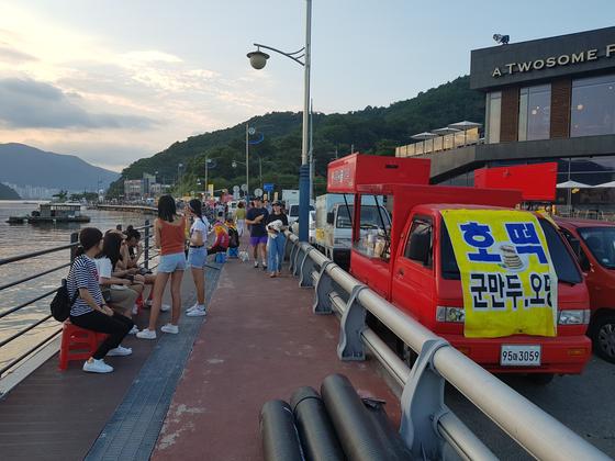 해안도로가에 있는 각종 푸드트럭 앞에서 사람들이 음식을 먹고 있다. 위성욱 기자