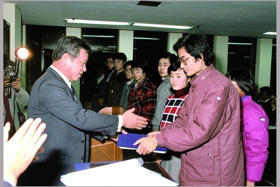 1986년 한국고등교육재단 장학생들에게 장학증서를 전달하는 최종현 회장(왼쪽). [사진 SK그룹]