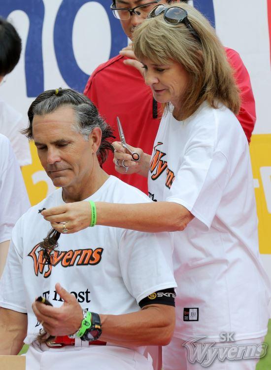 소아암 어린이를 위해 모발 기부를 하기 위해 머리를 자르고 있는 트레이 힐만 SK 감독. 오른쪽은 커트를 도와주고 있는 힐만 감독의 아내 마리 여사. [사진 SK 와이번스]