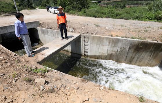 충남 예산군 신양면 차동리에서 마을 주민들이 도수로를 통해 끌어온 물을 지켜보고 있다. 이 물은 하천을 따라 예당저수지까지 흘러간다. 프리랜서 김성태
