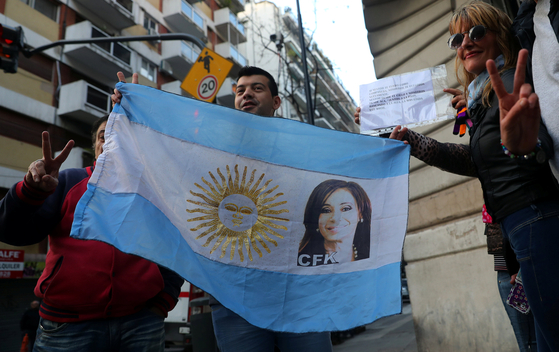 크리스티나 페르난데스 아르헨티나 전 대통령이 13일(현지시간) 부패스캔들과 관련한 법정에 출석하기에 앞서 지지자들이 그의 얼굴이 그려진 아르헨티나 국기를 흔들고 있다. [로이터=연합뉴스]