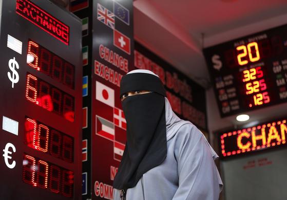 미국발 관세 쇼크에 휘청이는 터키 리라화가 13일(현지시간)에도 달러화 대비 장중 10% 가까이 급락하는 등 요동쳤다. 터키 중앙은행은 이날 지급준비율 인하를 통해 시중에 유동성을 공급하는 한편 외환 거래 제한 조치를 단행한다고 밝혔다. 니캅 차림의 여성이 이스탄불의 환전소 앞을 걷고 있다. [AP=연합뉴스]