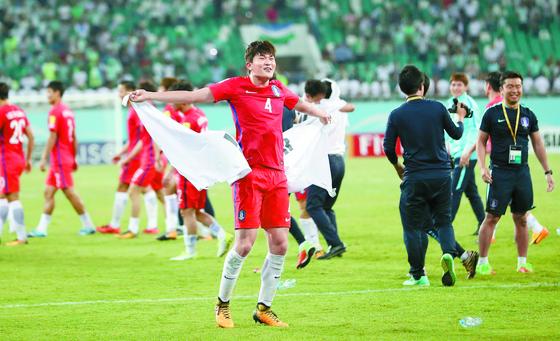 22세 젊은 수비수 김민재는 한국 축구가 믿고 쓰는 수비자원으로 진화했다. 지난해 9월 우즈베키스탄전에서 러시아 월드컵 본선행을 확정 지은 뒤 태극기를 펼쳐들고 기뻐하는 김민재. [연합뉴스]