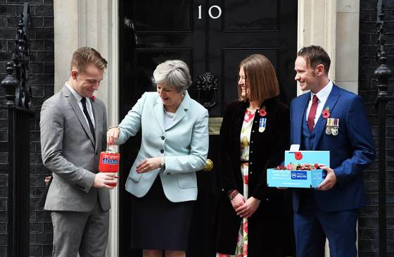 2017년 10월 30일 테레사 메이 영국 총리가 관저 앞에서 제1,2차 세계대전에서 희생된 장병들을 추모하는 '포피'를 가슴에 달기 위해 손을 뻗고 있다. [연합뉴스]