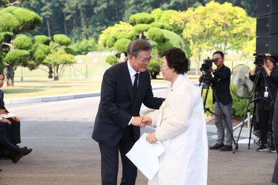 문재인 대통령이14일 충남 천안 국립 망향의 동산 모란묘역에서 열린 '일본군 위안부 피해자 기림의 날' 행사에서 이용수 할머니의 손을 잡고 있다. 청와대사진기자단
