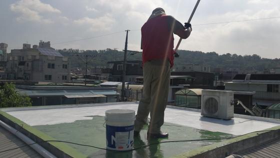 자원봉사자가 서울의 한 건물 옥상을 쿨루프 페인트로 칠하고 있다. [사진 십년후연구소]