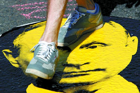 러시아 정부의 연금법 개정에 반대하는 한 시위자가 길바닥에 붙어 있는 푸틴 대통령의 얼굴 그림을 밟고 지나가고 있다. [AP=연합뉴스]