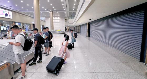 14일 오후 인천공항 제1터미널 입국장에서 승객들이 짐을 찾고 있다. 그 뒤로 셔터가 내려진 면세점 예정 공간이 보인다. 이곳은 2001년 개항 때부터 입국장 면세점 예정 공간으로 마련돼 있었다. [연합뉴스]