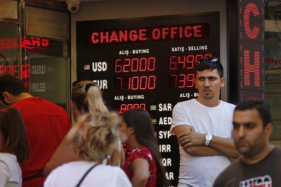 지난 14일(현지시간) 터키 이스탄불의 한 환전소에 돈을 바꾸려는 고객이 몰려들었다. 최근 미국과의 정치적 갈등으로 터키 리라화가 폭락하면서 세계 금융시장이 요동치고 있다. [이스탄불 AP=연합뉴스]