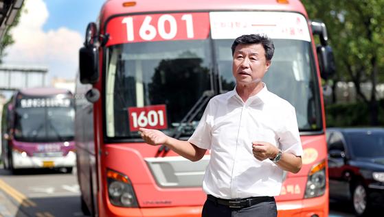 인천에서 버스 사업을 하는 신동완 선진여객 대표가 최저임금 인상 등으로 인한 광역버스 운행의 어려움을 토로하고 있다. 뒤에 보이는 빨간색 버스가 인천과 서울을 오가는 광역버스 중 하나다. [변선구 기자]