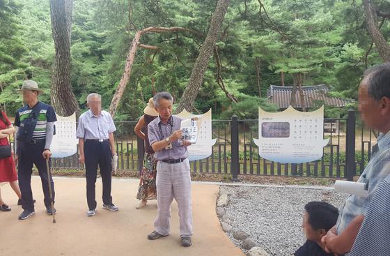 박석홍 전 소수박물관장(가운데 글자판 든 사람)이 소수서원 입구에서 관련 역사를 설명하고 있다. 뒤로 세한도의 소재가 된 취한대와 학자수가 보인다. [사진 송의호]