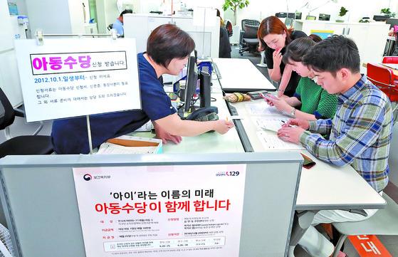 지난 6월 20일 서울 서대문구 남가좌1동 주민센터에서 한 부부가 오는 9월부터 아동 1명당 월 10만원씩 지급되는 아동수당을 신청하고 있다. [연합뉴스]