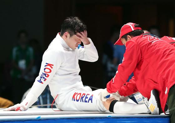 17일 자카르타 팔렘방 아시안게임 남자 펜싱 에페 개인전 결승전에서 한국 박상영이 무릎 통증으로 주저앉아 있다. 자카르타=김성룡 기자