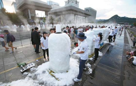 크라운해태제과가 지난달 12일 광화문광장에서 개최한 '한여름 밤의 눈조각전'에 참여한 임직원들이 300개의 눈조각을 만들고 있다.