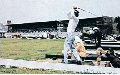 뚝섬 경마장 트랙 안에 있던 골프연습장. 캐디가 공을 놓아 주는 모습이 이채롭다. 뒤로는 경마장 관중석이 보인다. [중앙포토]