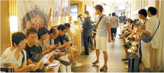 더위를 아랑곳하지 않고 마냥 기다리는 일본인들. 기다리는 손님들에게 종업원은 메뉴를 설명해 준다.[사진 장상인 대표]