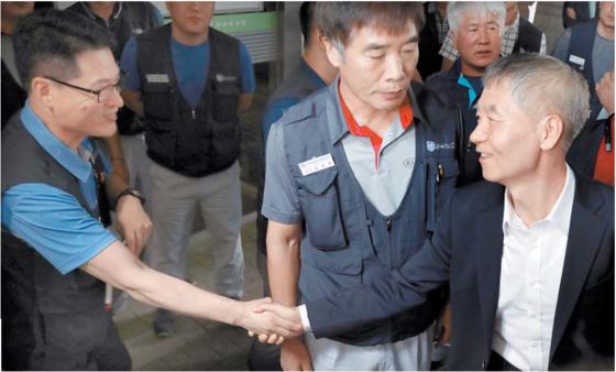 지난달 31일 통상임금 1심 판결 직후 기아차 노조 대표(왼쪽)가 노조 측 변호사와 악수하고 있다. [연합뉴스]