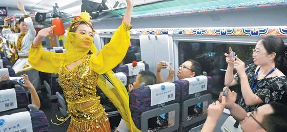 7월 9일 개통한 중국 서부 란저우~바오지 간 고속열차에서 승객들이 소수민족 공연을 즐기고 있다. 우루무치를 비롯한 신장웨이우얼 자치구는 중국 중심부와 고속열차로 연결됐다. [신화=연합뉴스]