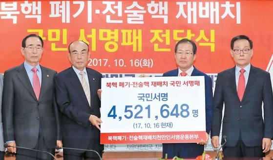 홍준표 자유한국당 대표가 지난 16일 서울 여의도 당사에서 '북핵 폐기·전술핵 재배치 1000만인 서명운동본부'로부터 452만여 명의 서명패를 전달받고 있다. [연합뉴스]