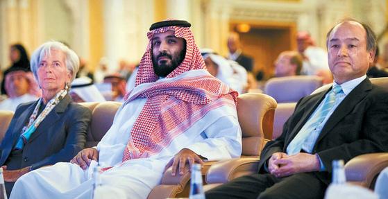 사우디아라비아의 왕세자인 무함마드 빈 살만 알사우드(가운데)가 지난달 24일 수도 리야드에서 열린 '미래투자 이니셔티브' 콘퍼런스에서 크리스틴 라가르드 국제통화기금(IMF) 총재(왼쪽), 손정의 일본 소프트뱅크 회장(오른쪽)과 나란히 앉아 있다. 무함마드 왕세자는 극보수적인 왕국을 '온건한 이슬람 국가'로 되돌리겠다고 말했다. [AP=연합뉴스]