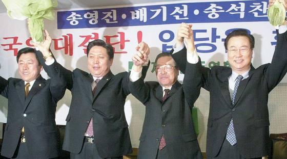 2000년 12월 30일 새천년민주당 의원 3명이 자민련 입당 후 김종필 자민련 명예총재(왼쪽 셋째)와 손을 들어올리고 있다. [중앙포토]