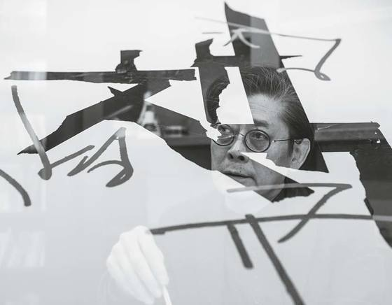 삼례책마을에서 열리고 있는 '정병규 책박물관디자인 17년'전의 포스터와 함께한 정병규 한글연구소장. 검은 마스킹테이프로 한글 '책'을 쓴 실험작업 '테이핑 타이포그래피'에 '정병규' 서명을 얹었다. 권혁재 사진전문기자