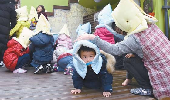 22일 서울 중구의 한 어린이집에서 지진대응 훈련이 진행됐다. 어린이들이 머리 보호를 위해 방재모자를 쓰고 있다. [사진 서울 중구청]