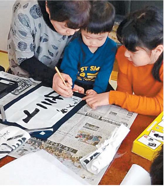 붓글씨로 신년휘호를 쓰는 아이들.