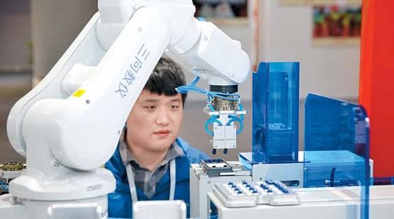중국은 창업과 기술혁신, 서비스 혁명으로 '세계의 공장'에서 벗어나려 한다. 지난해 12월 광저우에서 열린 해외인재박람회에서 로봇이 전자계산기를 조립하는 모습. [광저우 로이터=연합뉴스]