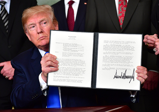 도널드 트럼프 미국 대통령이 22일(현지시간) 중국을 겨냥해 보호관세를 부과하기로 결정했다. 트럼프 대통령이 서명을 한 보호관세 행정명령을 들어보이고 있다. [워싱턴 UPI=연합뉴스]