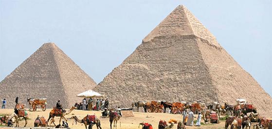 이집트의 피라미드 중에서 가장 웅장한 규모를 자랑하는 기자 피라미드 앞에서 낙타와 말들이 잠시 휴식을 취하고 있다. [중앙포토]